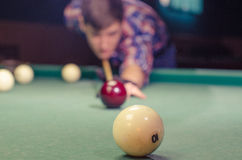 Boy preparing for shot the billiard ball with number ten 10. Boy is not in focus aiming for shot the billiard ball which are in focus Stock Photo
