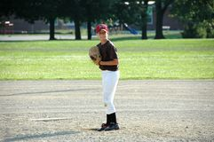 Boy preparing to pitch in youth baseball game. A young pitcher prepares to deliver the ball in a youth baseball game stock images