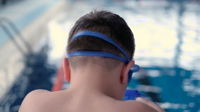 The boy is preparing to swim in the pool. Professional stock video footage