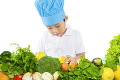 Boy preparing vegetables on table Stock Photography