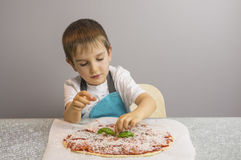 Boy is prepearing pizza Stock Image