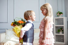 Boy is presented flowers to girl Royalty Free Stock Photos