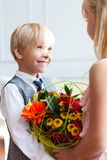 Boy is presenting flowers to girl Stock Images