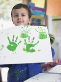Boy Presenting His Finger Painting In Class Stock Image