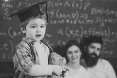 Boy presenting his knowledge to mom and dad. Support concept. Kid holds teddy bear and performing. Parents listening. Their son, chalkboard on background. Smart stock images