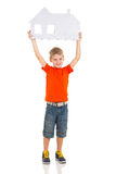 Boy presenting house. Caucasian boy presenting paper house on white background Royalty Free Stock Photo