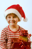 Boy and presents. Young boy with Christmas hat and presents stock photo