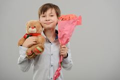 Boy with presents for crush. On gray. Cute Teddy bear toy and bouquet of roses. Perfect gift to melt her heart stock image