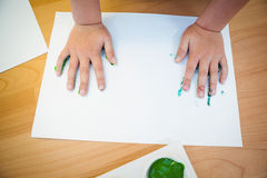 Boy pressing his paint covered hands Stock Photo