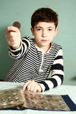 Boy preteen numismatic collector show  coin. Boy preteen numismatic collector show his coin with hole in the middle look through it close up portrait Royalty Free Stock Photography