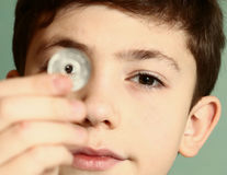 Boy preteen numismatic collector show  coin. Boy preteen numismatic collector show his coin with hole in the middle look through it close up portrait Stock Image