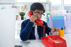 Boy pretending as businessman using land line phone. At desk in office Royalty Free Stock Images