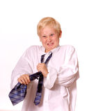 Boy Pretending to be Grown-Up Struggles with tie. Young Blond Boy Pretending to be Grown-Up Shows Frustration with Men's Tie.  Boy is wearing a man's white dress Royalty Free Stock Images
