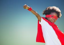 Boy pretending to be a superhero against blue background Royalty Free Stock Photos