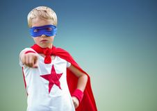Boy pretending to be a superhero standing against sky blue background Stock Image