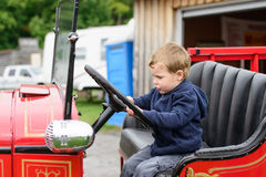 Boy Pretending to Drive an Old Fire Truck. A happy young boy sits in an old shiny vintage red fire truck holding on to the steering wheel pretending to drive Royalty Free Stock Photos