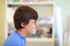 Boy in profile pulling mad funny face Royalty Free Stock Images