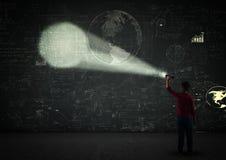 Boy with a projector. Kid using a flashlight in a dark room on a blackboard full of math formulas Royalty Free Stock Photos