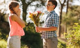 Boy proposing to his girlfriend with flowers royalty free stock photos