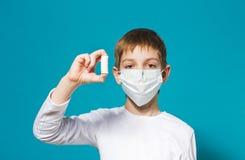 Boy protection mask holding pills Stock Photo