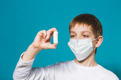 Boy in protection mask looking at pills Stock Photo
