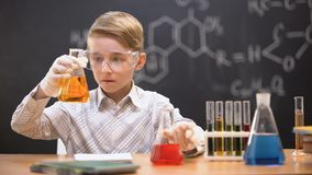 Boy in protective glasses mixing chemical liquids in flasks, curious genius