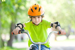 The boy in the protective helmet for bike. In summer park Stock Photo