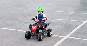 Boy in a protective helmet on the electric vehicle. Boy in a protective green helmet on the electric vehicle Royalty Free Stock Image