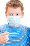 A boy in a protective mask with thermometer in hand. On a white background Royalty Free Stock Photography