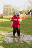 Boy in the puddle. Royalty Free Stock Photos