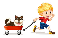 Boy pulling cart with dog on it Royalty Free Stock Photo