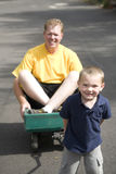 Boy pulling dad in wagon. A young boy pulling his dad in a wagon Royalty Free Stock Photography