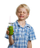 Boy pulling face holding green smoothie Royalty Free Stock Photo