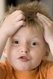 Boy pulling a funny face. Three year old boy pulling his hair and pulling a funny face Stock Image