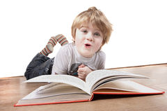 Boy pulling a funny face whilst reading book Stock Photo