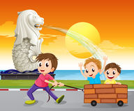 A boy pulling an improvised cart near  Merlion. Illustration of a boy pulling an improvised cart near the statue of the Merlion Stock Images