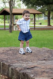 Boy Pulling Up Shorts At The Park Royalty Free Stock Image