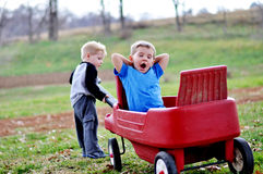 Boy pulling brother in red wagon. One young child pulling yawning boy in red wagon stock image