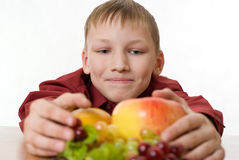 Boy pulls himself to the fruit Stock Images