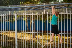 The boy pulls himself up on the crossbar. Outdoors royalty free stock images