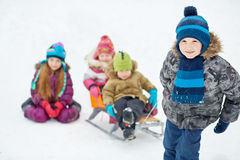 Boy pulls sledges with two younger children. Focus on boy Royalty Free Stock Images