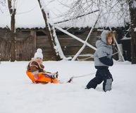 Boy pulls sledges with younger sister Stock Photography