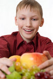Boy pulls to a lot of fruit Royalty Free Stock Photo