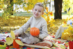 Boy with pumpkin in autumn park Royalty Free Stock Photos