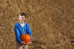 Boy with pumpkin. A boy in a blue jacket with orange pumpkin in his hands royalty free stock photo