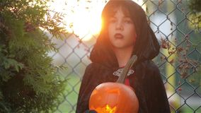 Boy with pumpkin dressed like vampire for Halloween party, Dracula holding pumpkin with a burning candle, background. Grid, outdoor, static stock footage