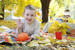 Boy with pumpkin greeting in park Royalty Free Stock Photos