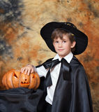 The boy with pumpkin for Halloween. The boy in black cloak with traditionally carved pumpkin for Halloween Stock Image