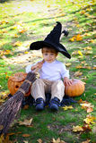 Boy with pumpkins, a broom and a hat Stock Photography