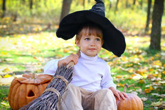 Boy with pumpkins, a broom and a hat Royalty Free Stock Photo